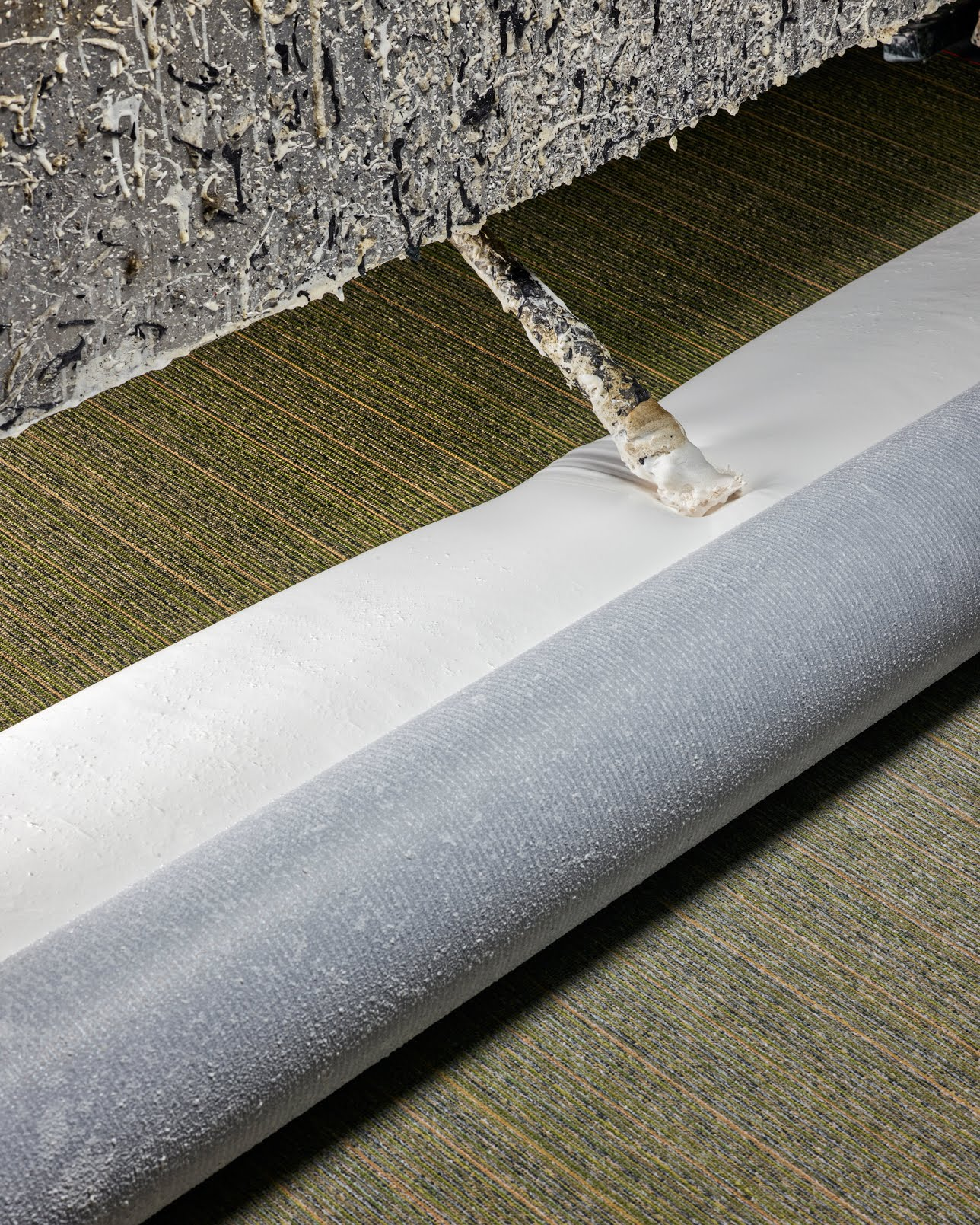 Adding latex created from smokestack exhaust to the tufted carpet.