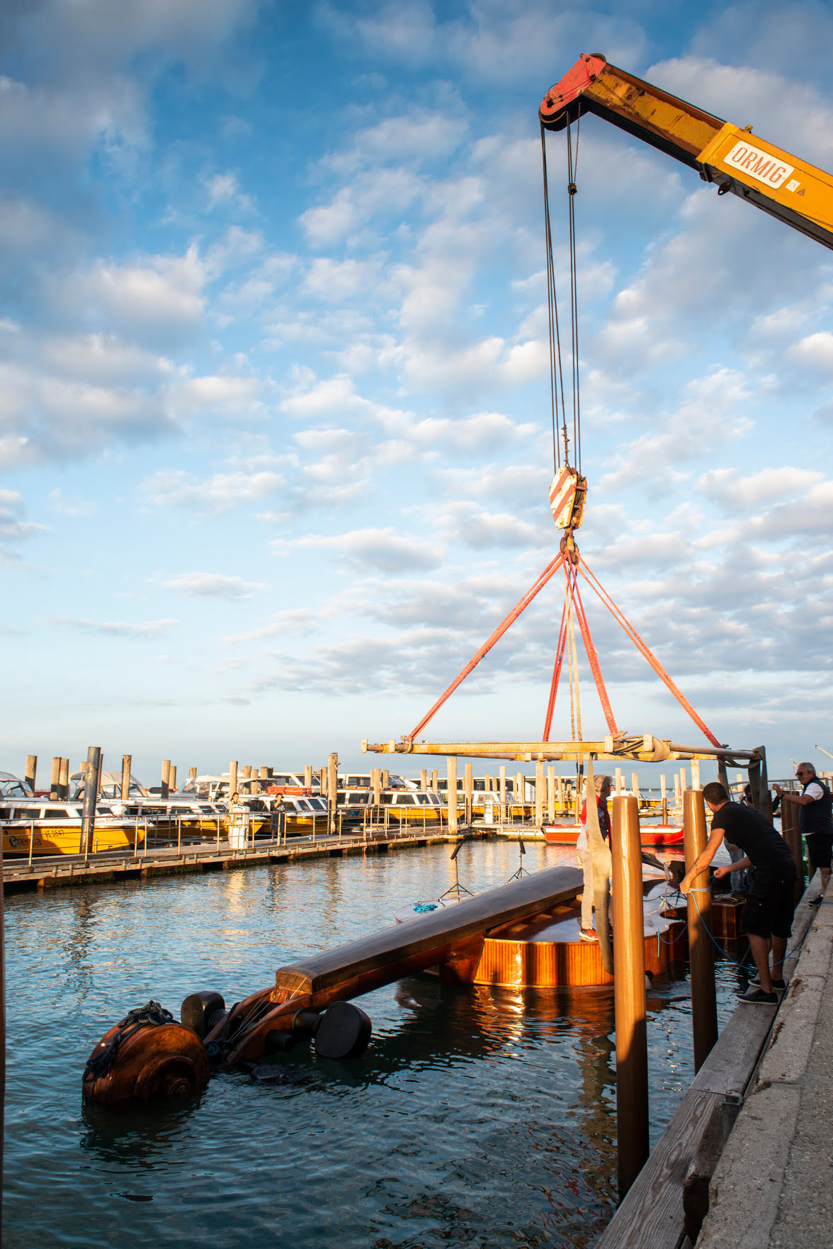 The violin being lowered into the lagoon. The artwork is a large-scale replica of a real violin.